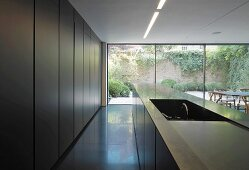 Open-plan kitchen with island opposite fitted cupboards and floor-to-ceiling glass wall with view of terrace