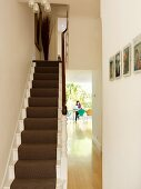 Traditional stairwell with view through open doorway into dining room