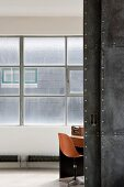 View through open sliding door into room with orange shell chair below industrial window