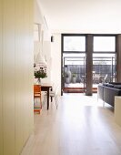 Open-plan living and dining room with floor-to-ceiling terrace windows