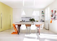 White chairs at rustic wooden table in modern kitchen