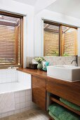 Corner of bathroom with fitted bathtub and modern washstand with wooden cabinet