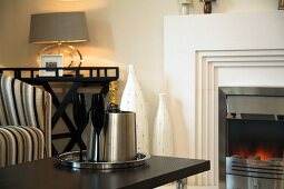 Champagne and glasses on coffee table in front of fireplace