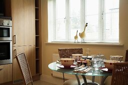 Table set for breakfast below window with half-closed blinds in kitchen