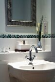 Sink below tiled shelf with border and framed mirror