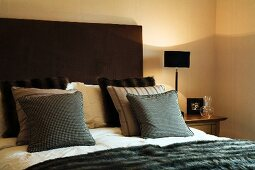 Stacks of scatter cushions against upholstered headboard