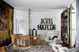 Fireguard around free-standing wood-burning stove in small, retro living room with artistic mixture of furniture