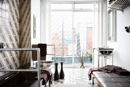 View of city roofscape through floor-to-ceiling glass wall in unconventional bathroom with stainless steel frames and leather couch