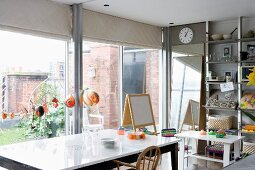 Dining area with simple, modern furniture and children's playthings in front of glass wall leading to courtyard garden