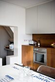 Modern kitchen unit in fine wood with white suspended cupboards and table top with printed underground map