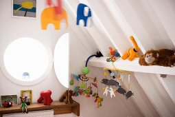 Bulls-eye window, soft toys and colourful mobile under white-painted roof structure in modern child's bedroom