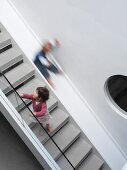Unconventional staircase design with bulls-eye window and slide alongside classic modern stairs with glass balustrade