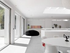 Dining area with classic designer pieces and oversized beanbag in white, sunny room with skylight and long glass wall with sliding doors