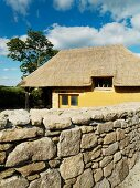 Clay house with thatched roof behind stone wall