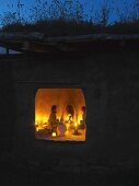Clay house with green roof at dusk - view into interior lit by fire in fireplace and candlelight