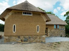Rustic building in organic style with thatched roof above clay and stone facade