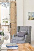 Grey, upholstered armchair in corner of room next to open interior door