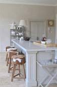 Bar stools with animal skin covers in front of heavy kitchen island with marble top