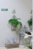 Metal watering can on floor next to metal-framed chair