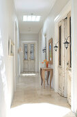 Narrow hallway in traditional country house with glass panels in doors and rustic console table