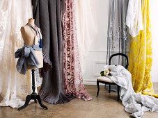 Tailor's dummy in front of hanging lengths of material with various patterns in traditional setting