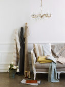 Bolts of cloth leant on wall next to antique sofa in traditional setting