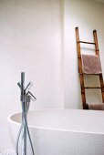 Bathroom with free-standing bathtub, floor-mounted tap fittings and ladder as towel rack