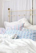 Country-house-style pillows against metal frame of old bed