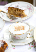 A cappuccino in an antique floral teacup surrounded by blurred plates of cake