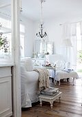 View into romantic living room with seating upholstered in white and rustic wooden floor