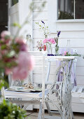 Vase of garden flowers on terrace table in front of white summer house
