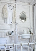 Vintage washbasin and jug on metal stand and shirt on clothes hanger on white-painted wooden wall