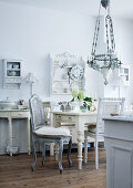 Antique kitchen lamp above table and antique chairs painted light grey in rustic dining room