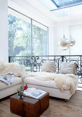 Comfortable sofa corner on bright gallery in house with solid wood floorboards and panoramic windows