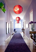 Three red Foscarini pendant lamps and antique console tables in lilac, eclectic ambiance of long period hallway