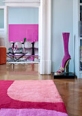 Detail of rug in shades of pink and lilac and shoe-shaped sculpture; dining area in background with white Panton chairs in front of pink painting