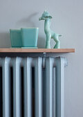 Pastel blue porcelain ornaments on cover of ribbed radiator