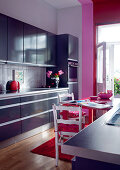 Modern fitted kitchen in muted blue combined with pink and red accents and vintage chairs