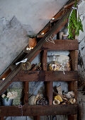 Christmas decorations on dark-stained wooden shelves under stairs