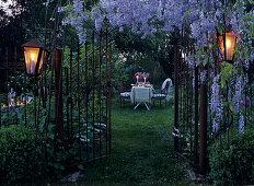 Garden gate below lavishly flowering, purple wisteria and garden table set for romantic evening in background