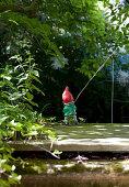 Gartenzwerg beim Angeln im Garten