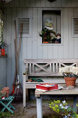 Sitzplatz mit einer Holzbank vor dem Gartenhaus