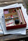 Kiste mit verschiedenen Fächern und Spielkarten auf Zeitung