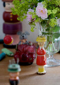 Knitting dollies and antique toys next to vase of flowers