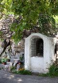 Tiny chapel next to stone steps on mountain road