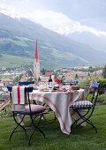 Gedeckter Tisch im Garten mit Blick auf die Ortschaft Schlander mit Kirchturm und auf die Bergkette