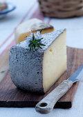 Ein Stück Südtiroler Käse mit Messer auf Holzbrett