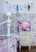 Child's bed with quilt next to rustic bedside cabinet against half-height Toile de Jouy wallpaper