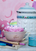 Pink flower in vintage teacup in front of vintage-style enamelled metal container