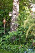 Vogelhäuschen am Baumstamm, daneben Keramikdeko
